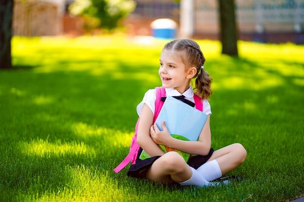 Menina da escola com mochila rosa sentado na grama depois das lições, olhando de lado, ler livro ou estudar lições