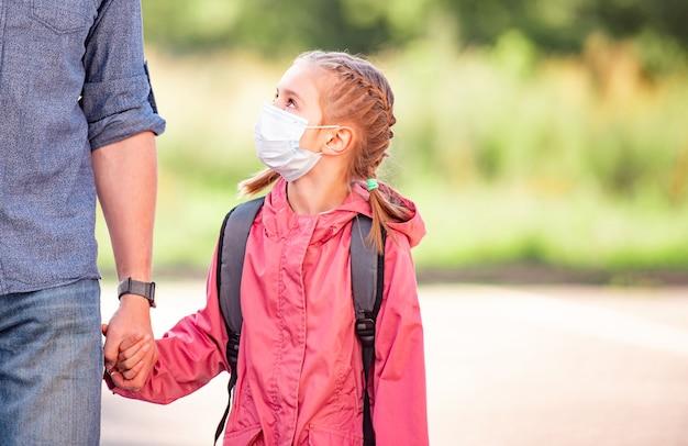 Menina da escola com o pai com máscaras médicas voltando para a escola