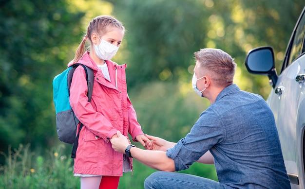Menina da escola com pai mascarado se encontrando após as aulas ao ar livre perto do carro