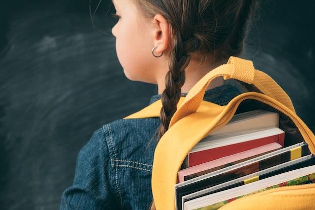 Menina da escola com rabo de cavalo carregando o verso amarelo com livros