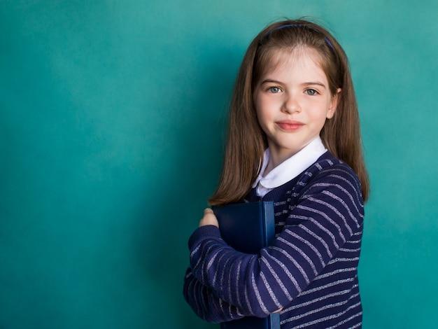 Menina da escola com um caderno sobre um fundo verde conselho escolar cchildren e conceito de escola
