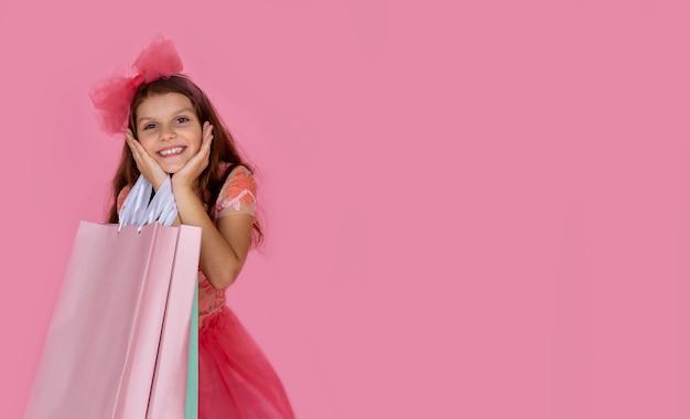 Menina da escola com um vestido rosa e feliz com sacolas de compras na mão
