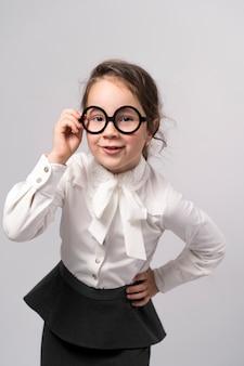 Menina da escola de primeiro grau em uma camisa branca e óculos olha para o quadro