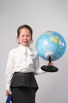 Menina da escola de primeiro grau em uma camisa branca segura um globo nas mãos e chora