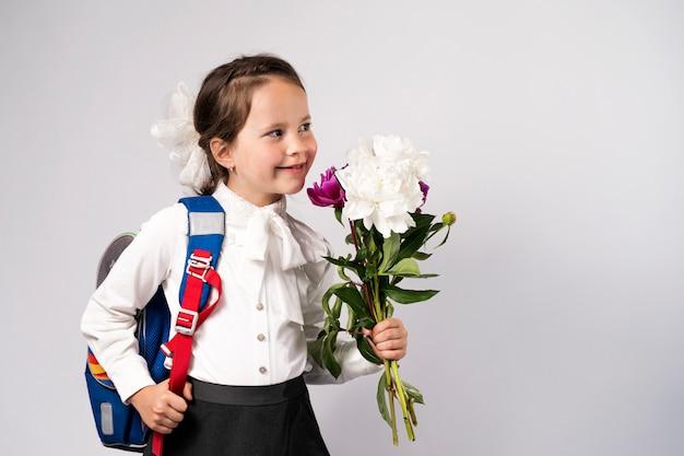 Menina da escola de primeiro grau em uma camisa branca segurando flores e uma mochila