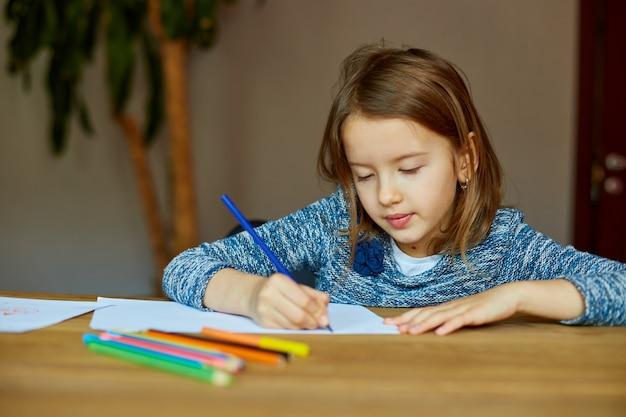 Menina da escola desenhando e escrevendo uma imagem com giz de cera, usando lápis de cor