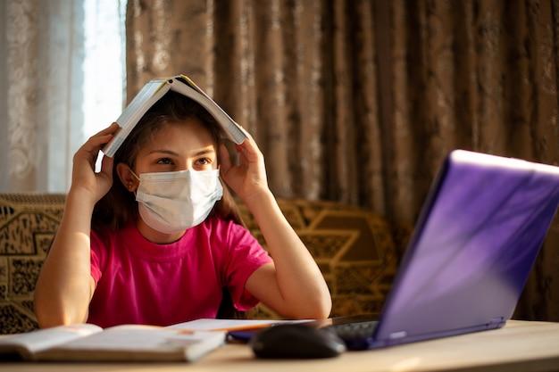 Menina da escola em máscara médica com uma cara triste em uma mesa trabalhando no laptop, doente e cansado de constante aprendizado, estudando, fazendo tarefas