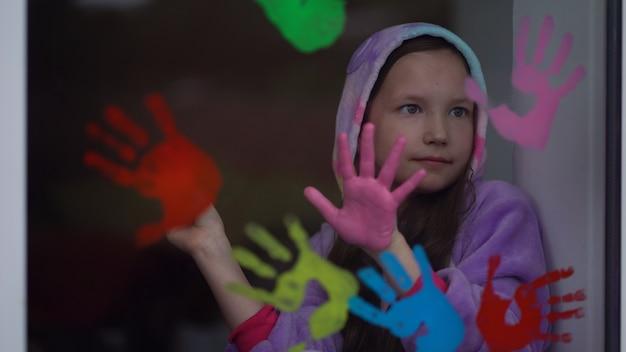 Menina da escola em pintura de pijama com as palmas das mãos na janela. quarentena fique em casa