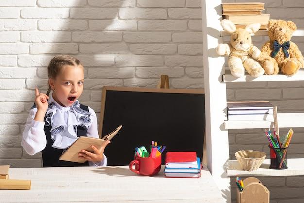 Menina da escola engraçada lendo livro em sala de aula no retrato da escola da adorável menina da escola em sala de aula em ...