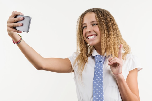 Menina da escola faz selfie usando smartphone