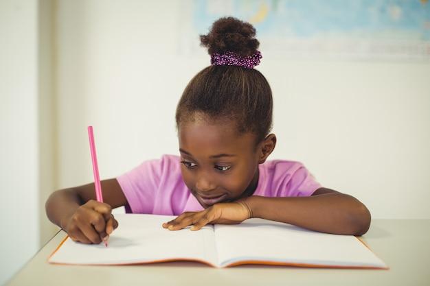 Menina da escola fazendo lição de casa em sala de aula
