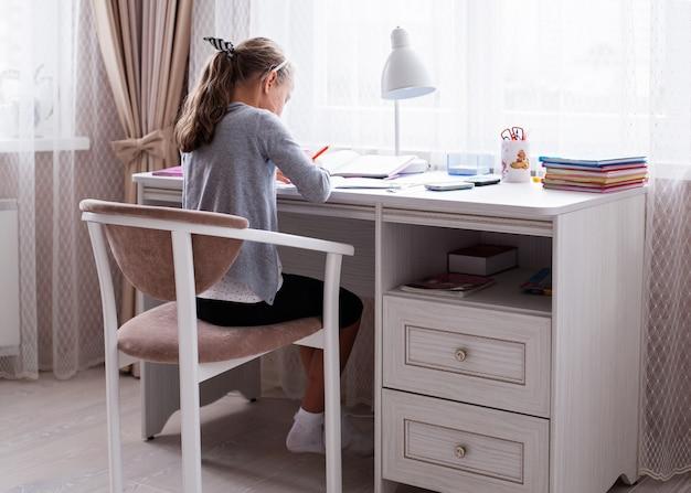 Menina da escola fazendo lição de casa na mesa