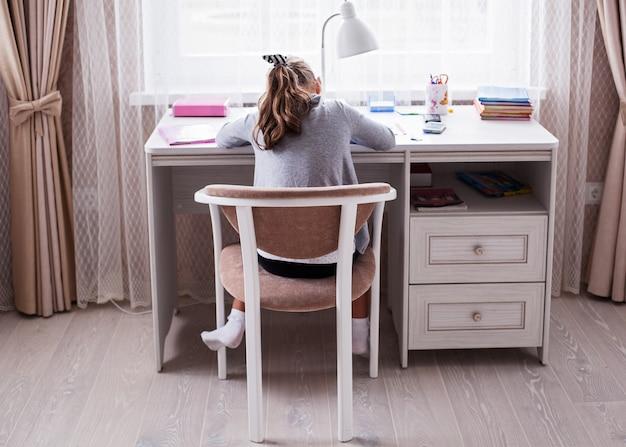 Menina da escola fazendo lição de casa