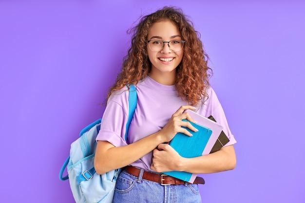 Menina da escola feliz com bolsa e livros posando para a câmera isolada sobre o roxo