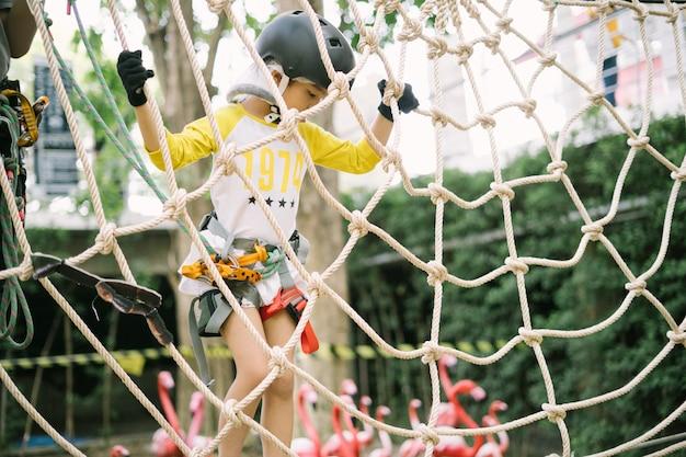 Menina da escola feliz desfrutando de atividade em um parque de aventura