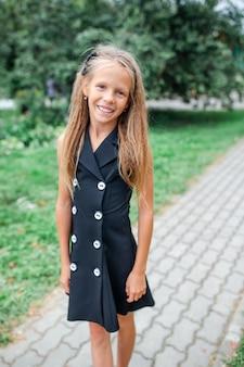 Menina da escola feliz posando na escola ourdoors