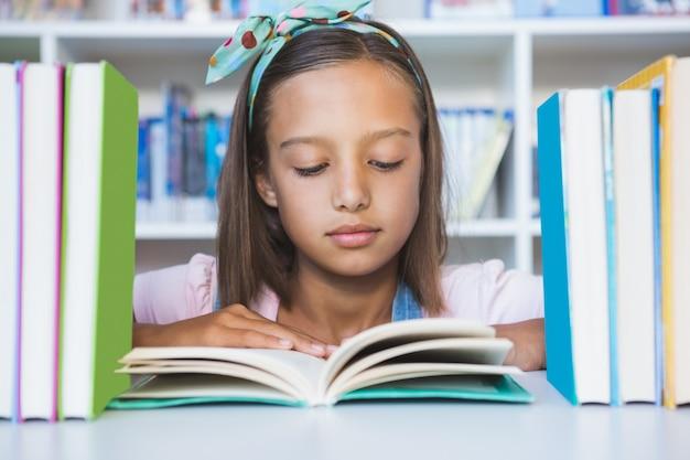 Menina da escola lendo um livro na biblioteca