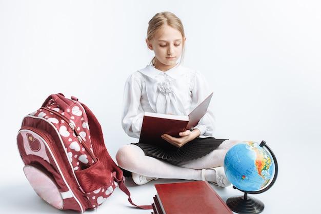 Menina da escola menina bonitinha sentada com livros e um globo, lendo um livro