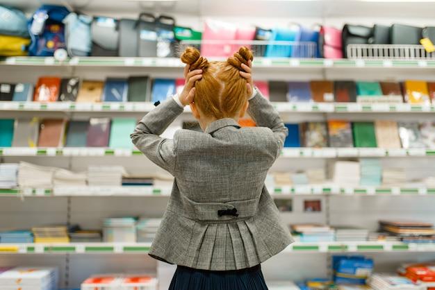 Menina da escola na prateleira de uma papelaria, vista traseira