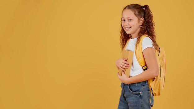 Menina da escola parada de lado copiar o espaço