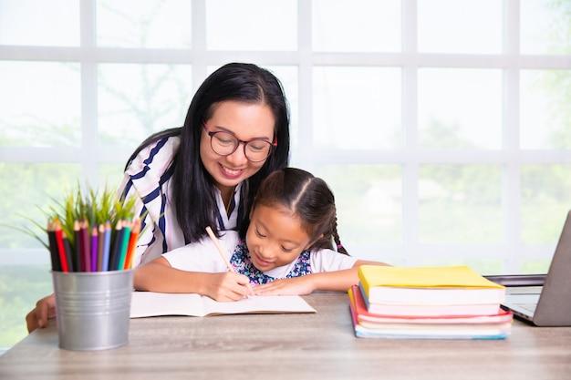Menina da escola primária estudando com o professor na classe