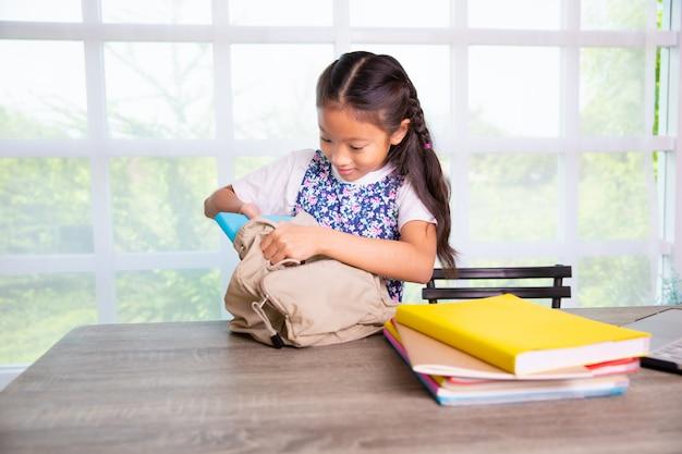 Menina da escola primária, livros de embalagem para os sacos