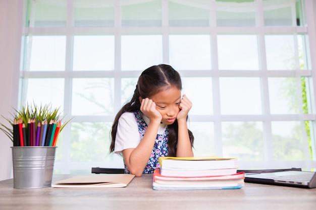 Menina da escola primária se sentir chato de estudar