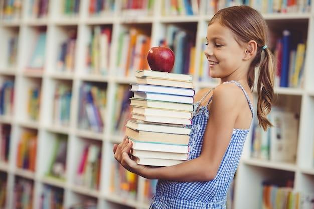 Menina da escola segurando a pilha de livros na biblioteca