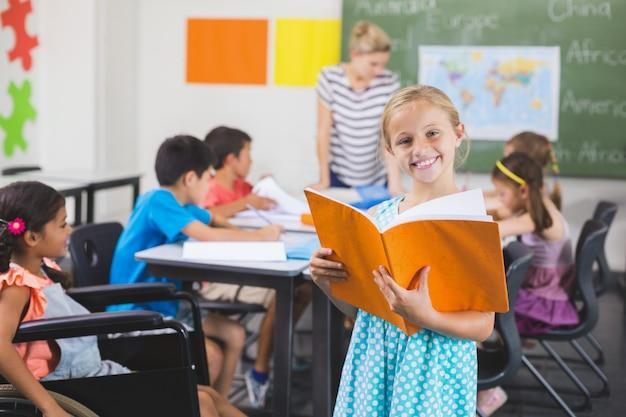 Menina da escola segurando um livro na sala de aula