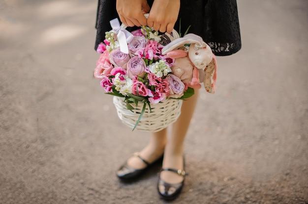 Menina da escola segurando uma cesta de vime fofa cheia de flores cor de rosa brilhantes, decoradas com um coelho de brinquedo