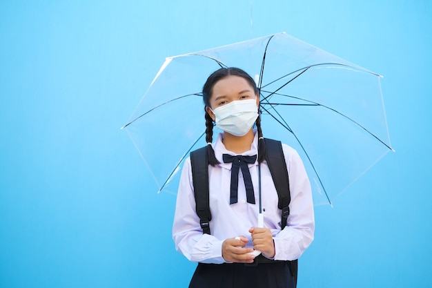 Menina da escola usa máscara com guarda-chuva sobre fundo azul