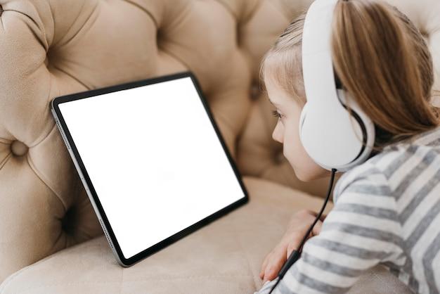 Menina da escola usando fones de ouvido e participando de aulas online