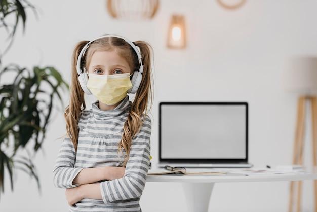 Menina da escola usando máscara médica dentro de casa