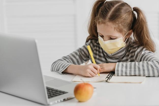 Menina da escola usando máscara médica