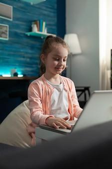 Menina da escola usando tecnologia de laptop para internet