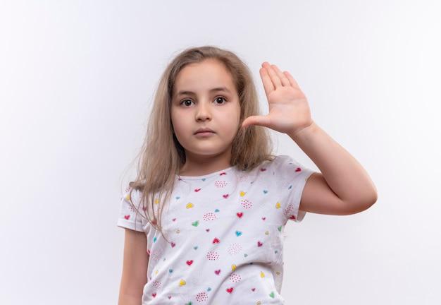 Menina da escola vestindo camiseta branca levantando a mão na parede branca isolada