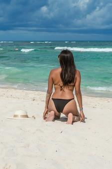 Menina da moda, ajoelhando-se na areia, olhando o mar azul em uma bela tarde. mulher vestindo maiô nas costas dela. parte traseira do atraente mulher olhando para o mar. chapéu de sol com laço na areia.