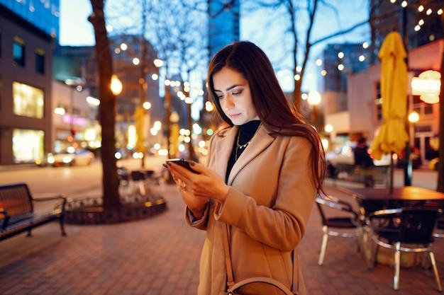 Menina da moda andando em uma cidade de noite