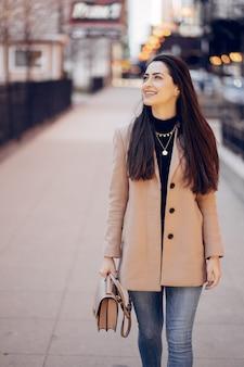 Menina da moda andando em uma cidade sping
