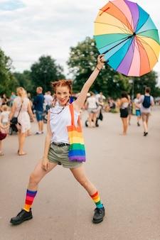 Menina da moda com bandeira de orgulho gay lgbt no rosto, posando com guarda-chuva na rua.