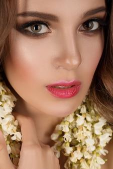 Menina da moda com flores no cabelo dela