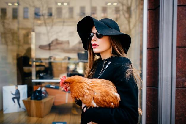 Menina da moda com frango nas mãos na grelha da vitrine de botique.