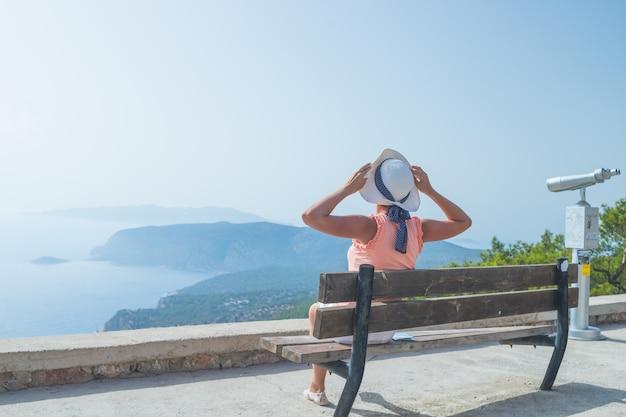 Menina da moda em chapéu branco senta-se em um banco e goza de vista para o mar e as montanhas.