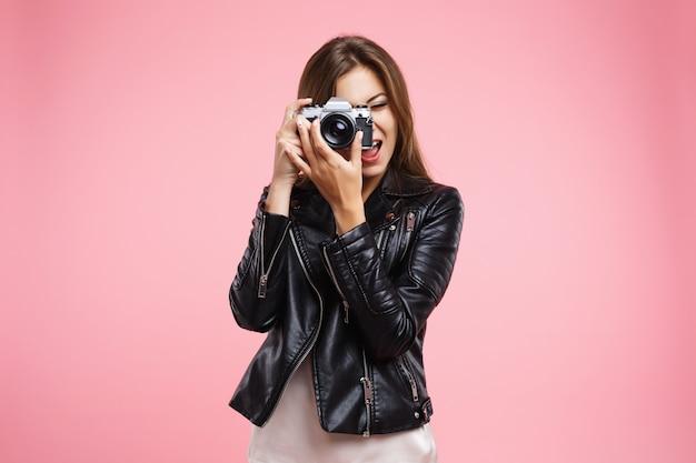 Menina da moda em jaqueta de couro preta, segurando a câmera antiga