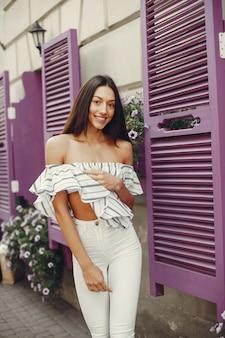 Menina da moda em pé em uma cidade de verão