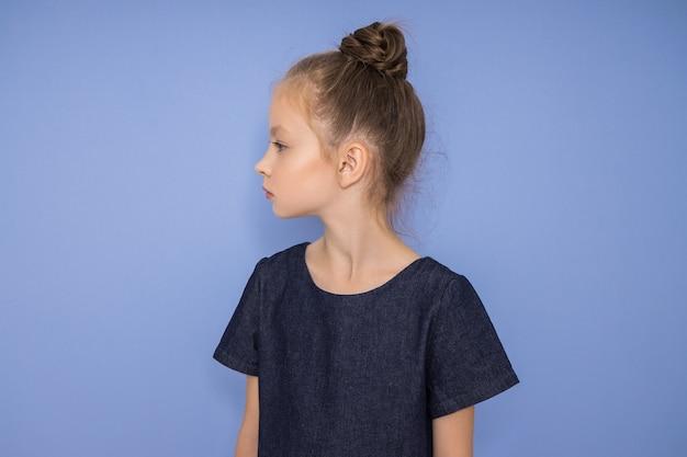 Menina da moda em roupas elegantes em fundo colorido de parede