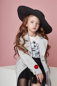 Menina da moda em roupas elegantes na parede colorida