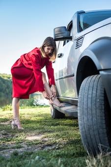 Menina da moda em um elegante vestido vermelho em pé perto de seu carro moderno e relaxar na natureza