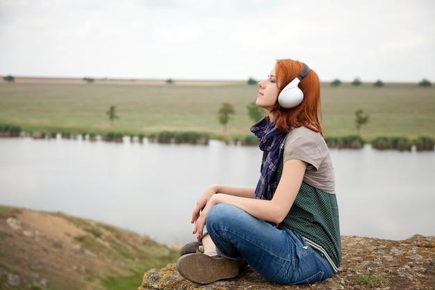 Menina da moda jovem com fones de ouvido na rocha perto do lago.