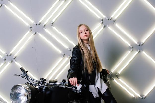 Menina da moda jovem posando em um couro preto com motocicleta.